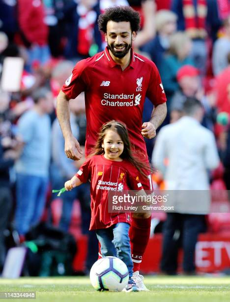 Liverpool's Mohamed Salah plays football with his daughter on the Anfield pitch at the final whistle during the Premier League match between...