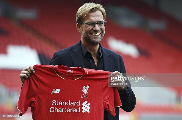 Liverpool's new German manager Jurgen Klopp poses with a team jersey after a press conference to announce his new appointment at Anfield in Liverpool...