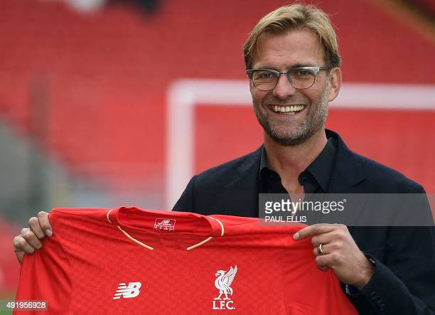 Liverpool's new German manager Jurgen Klopp poses with a team jersey after a press conference to announce his new appointment at Anfield in...