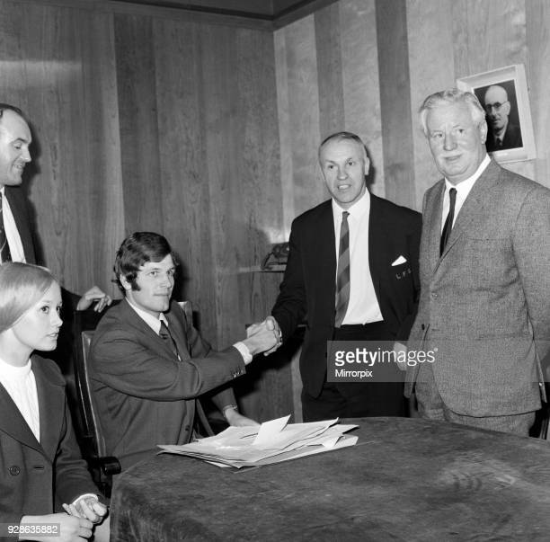 Liverpool's new signing John Toshack from Cardiff City signs his contract accompanied by his wife Susan at Anfield Looking on are manager Bill...