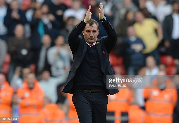 Liverpool's Northern Irish manager Brendan Rodgers applauds as he walks onfield after the final whistle of the English Premier League football match...