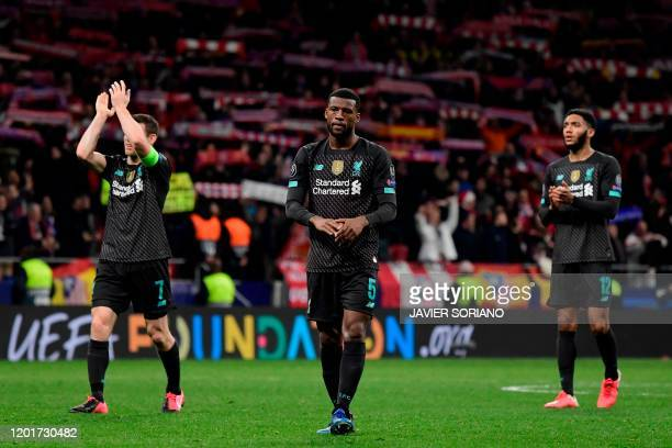 Liverpool's players applaud to fans at the end of the UEFA Champions League round of 16 first leg football match between Club Atletico de Madrid and...