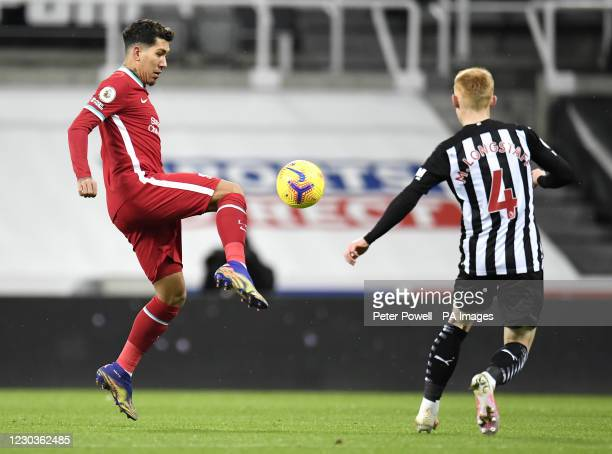 Liverpool's Roberto Firmino and Newcastle United's Matty Longstaff battle for the ball during the Premier League match at St James' Park, Newcastle.