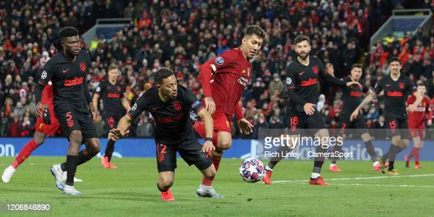 Liverpool's Roberto Firmino battles with Atletico Madrid's Renan Lodi during the UEFA Champions League round of 16 second leg match between Liverpool...