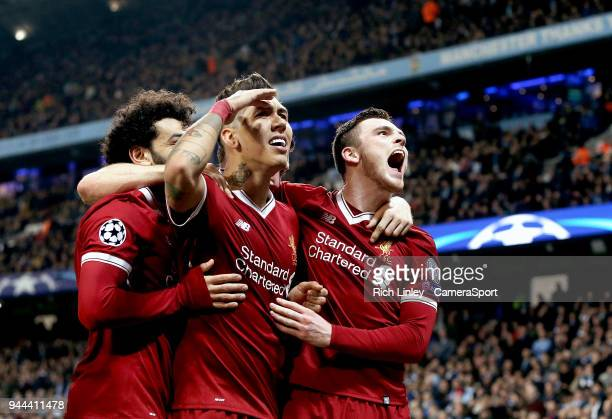 Liverpool's Roberto Firmino celebrates with teammates Mohamed Salah and Andrew Robertson after scoring his side's second goal during the UEFA...