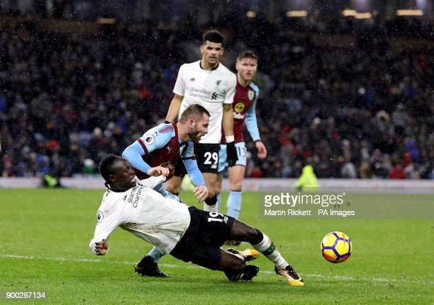 Liverpool's Sadio Mane goes down in the penalty area under a challenge from Burnley's Phil Bardsley during the Premier League match at Turf Moor...