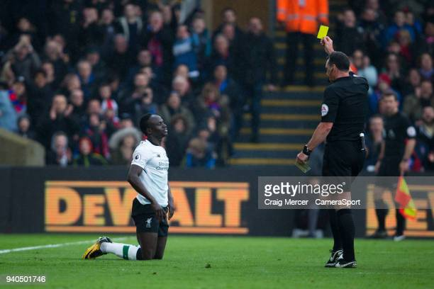 Liverpool's Sadio Mane is booked for simulation by Referee Neil Swarbrick during the Premier League match between Crystal Palace and Liverpool at...