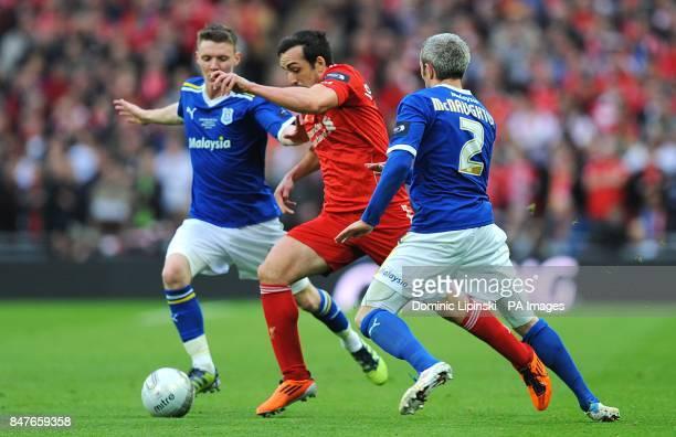 Liverpool's Sanchez Jose Enrique runs at Cardiff City's Kevin McNaughton and Joe Mason