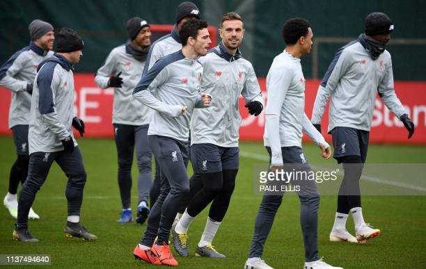 Liverpool's Scottish defender Andrew Robertson and Liverpool's English midfielder Jordan Henderson takes part in a team training session at Melwood...