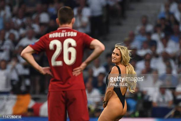 Liverpool's Scottish defender Andrew Robertson looks at a pitch-invader running on the pitch during the UEFA Champions League final football match...