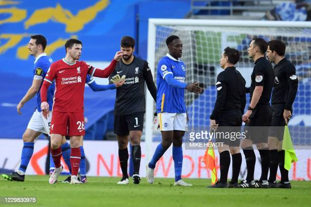 Liverpool's Scottish defender Andrew Robertson speaks to referee Stuart Attwell after the English Premier League football match between Brighton and...