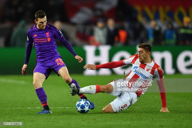 Liverpool's Scottish defender Andrew Robertson vies for the ball with Liverpool's Brazilian forward Roberto Firmino during the UEFA Champions League...