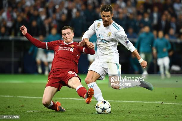 TOPSHOT Liverpool's Scottish defender Andrew Robertson vies for the ball with Real Madrid's Portuguese forward Cristiano Ronaldo during the UEFA...