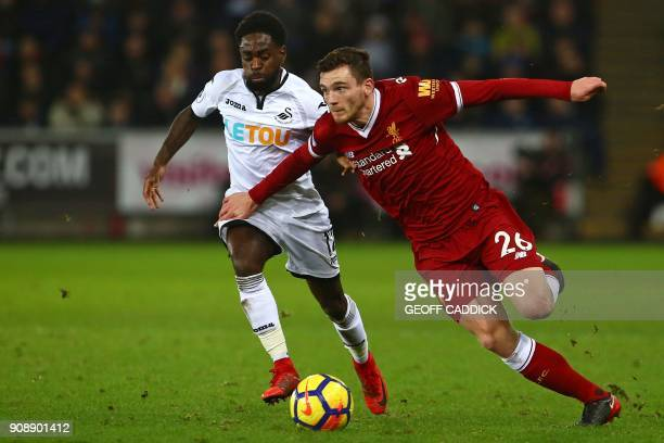 Liverpool's Scottish defender Andrew Robertson vies with Swansea City's English midfielder Nathan Dyer during the English Premier League football...
