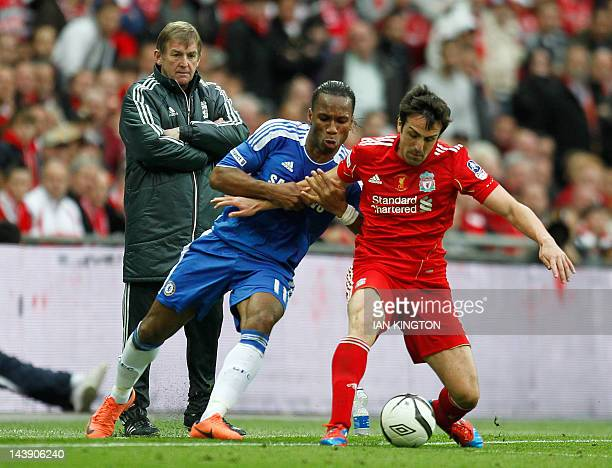 Liverpool's Scottish manager Kenny Dalglish looks on as Liverpool's Spanish defender Jose Enrique vies with Chelsea's Ivorian striker Didier Drogba...