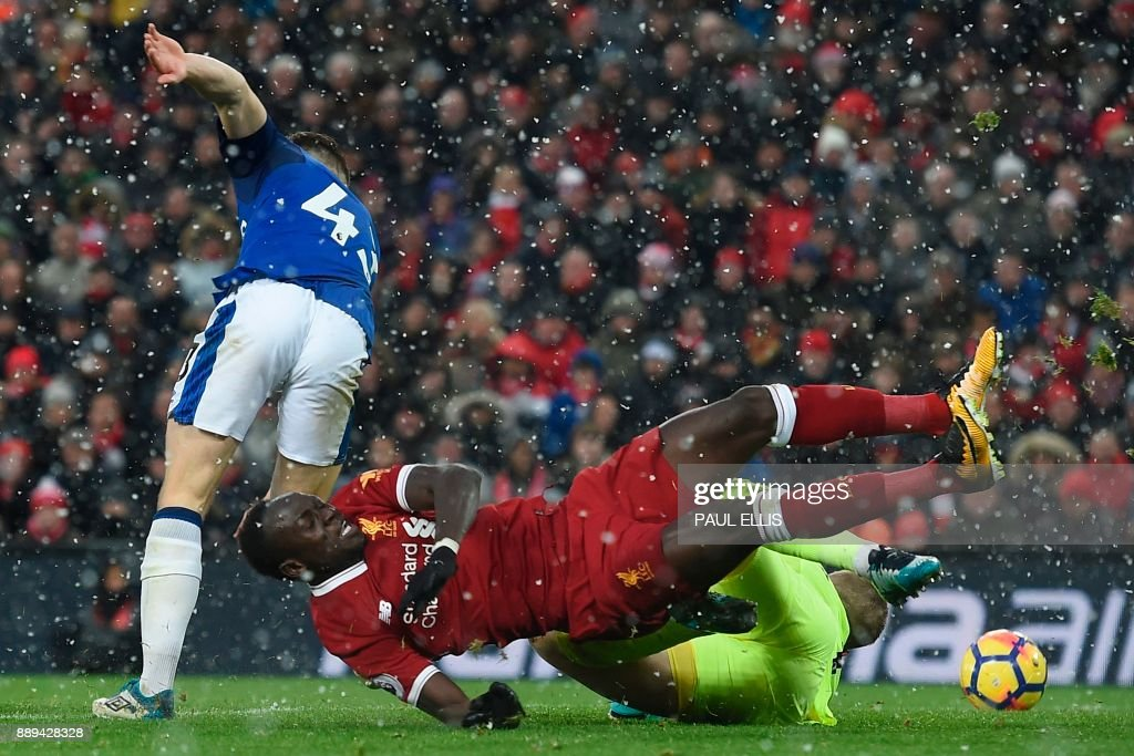 TOPSHOT - Liverpool's Senegalese midfielder Sadio Mane (C) flies in to try to reach a cross as Everton's English goalkeeper Jordan Pickford (R) and Everton's English midfielder Jonjoe Kenny (L) defend during the English Premier League football match between Liverpool and Everton at Anfield in Liverpool, north west England on December 10, 2017. / AFP PHOTO / PAUL ELLIS / RESTRICTED TO EDITORIAL USE. No use with unauthorized audio, video, data, fixture lists, club/league logos or 'live' services. Online in-match use limited to 75 images, no video emulation. No use in betting, games or single club/league/player publications. /