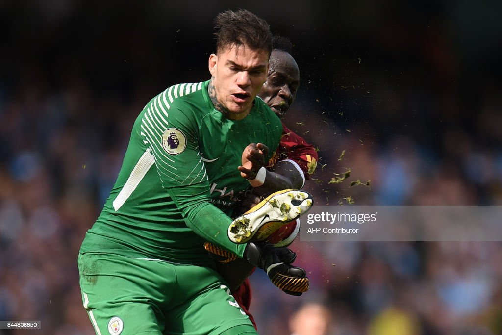TOPSHOT - Liverpool's Senegalese midfielder Sadio Mane (R) is sent off for this challenge on Manchester City's Brazilian goalkeeper Ederson during the English Premier League football match between Manchester City and Liverpool at the Etihad Stadium in Manchester, north west England, on September 9, 2017. / AFP PHOTO / Oli SCARFF / RESTRICTED TO EDITORIAL USE. No use with unauthorized audio, video, data, fixture lists, club/league logos or 'live' services. Online in-match use limited to 75 images, no video emulation. No use in betting, games or single club/league/player publications. /