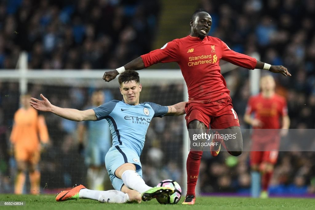 TOPSHOT - Liverpool's Senegalese midfielder Sadio Mane is tackled by Manchester City's English defender John Stones (L) during the English Premier League football match between Manchester City and Liverpool at the Etihad Stadium in Manchester, north west England, on March 19, 2017. / AFP PHOTO / Oli SCARFF / RESTRICTED TO EDITORIAL USE. No use with unauthorized audio, video, data, fixture lists, club/league logos or 'live' services. Online in-match use limited to 75 images, no video emulation. No use in betting, games or single club/league/player publications. /