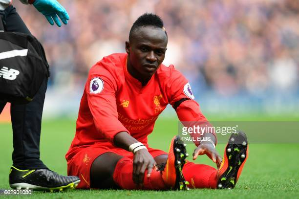 Liverpool's Senegalese midfielder Sadio Mane reacts after picking up an injury during the English Premier League football match between Liverpool and...