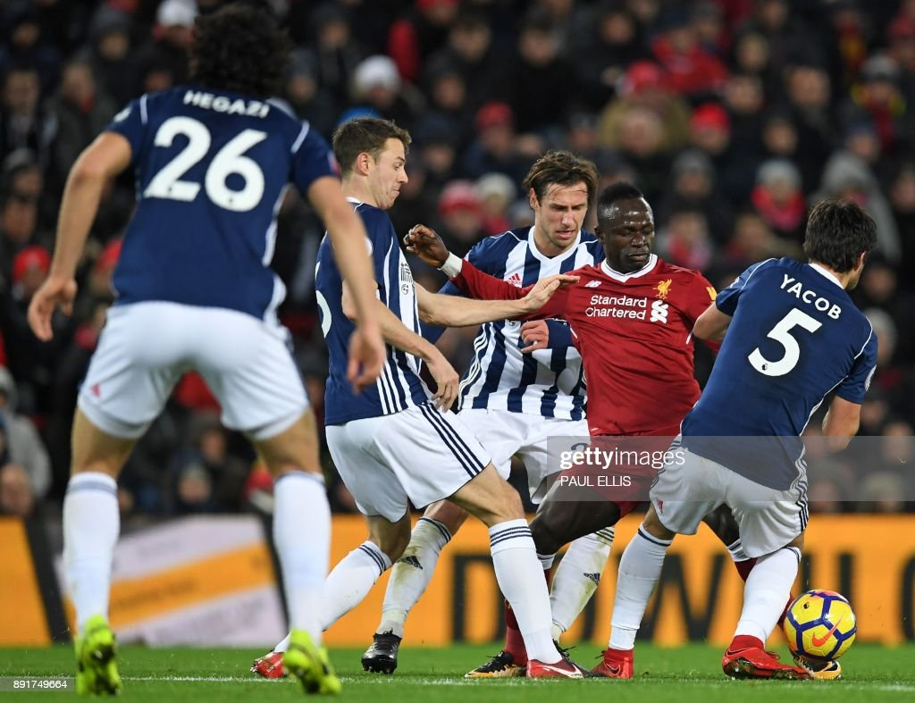 Liverpool's Senegalese midfielder Sadio Mane (2nd R) vies with West Bromwich Albion's Egyptian defender Ahmed Hegazy (L), West Bromwich Albion's Northern Irish defender Jonny Evans (2nd L), West Bromwich Albion's Polish midfielder Grzegorz Krychowiak (C) and West Bromwich Albion's Argentinian midfielder Claudio Yacob (R) during the English Premier League football match between Liverpool and West Bromwich Albion at Anfield in Liverpool, north west England on December 13, 2017. / AFP PHOTO / Paul ELLIS / RESTRICTED TO EDITORIAL USE. No use with unauthorized audio, video, data, fixture lists, club/league logos or 'live' services. Online in-match use limited to 75 images, no video emulation. No use in betting, games or single club/league/player publications. /