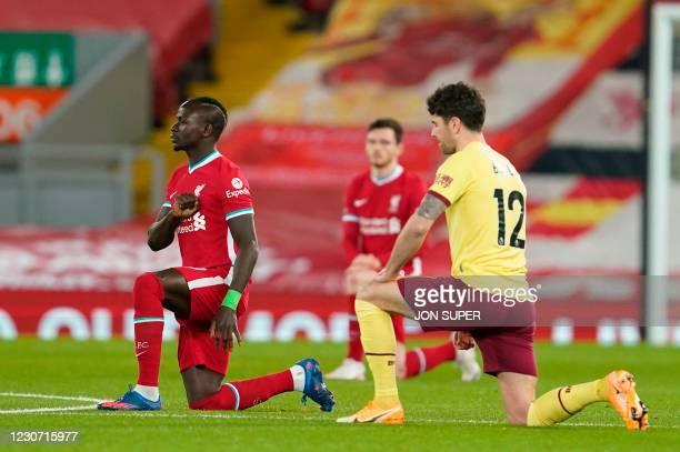 Liverpool's Senegalese striker Sadio Mane and Burnley's Irish midfielder Robbie Brady take a knee against racism during the English Premier League...