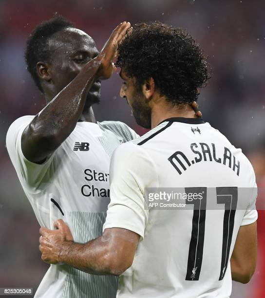 Liverpool's Senegalese striker Sadio Mane and his teammate Liverpool's Egyptian striker Mohamed Salah react after the second goal for Liverpool...