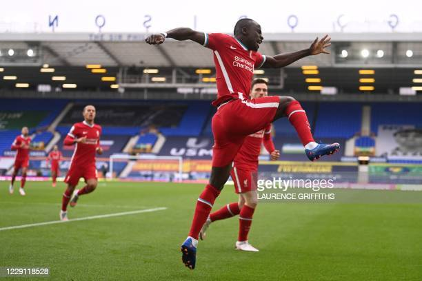 Liverpool's Senegalese striker Sadio Mane celebrates scoring his team's first goal during the English Premier League football match between Everton...