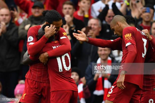 Liverpool's Senegalese striker Sadio Mane celebrates with Liverpool's Dutch defender Virgil van Dijk after he scored his team's first goal during the...