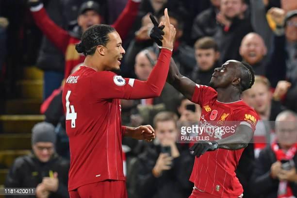 Liverpool's Senegalese striker Sadio Mane celebrates with Liverpool's Dutch defender Virgil van Dijk after scoring their third goal during the...