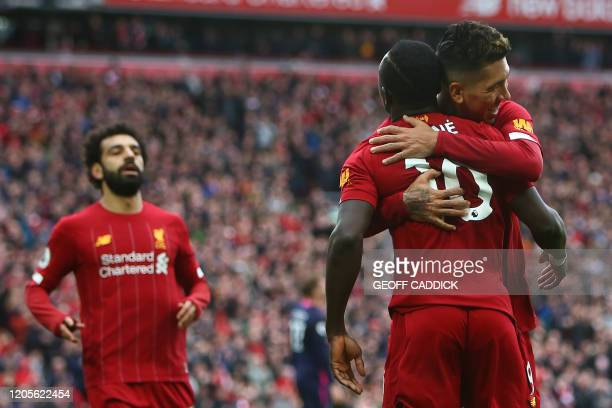 Liverpool's Senegalese striker Sadio Mane celebrates with Liverpool's Brazilian midfielder Roberto Firmino and Liverpool's Egyptian midfielder...