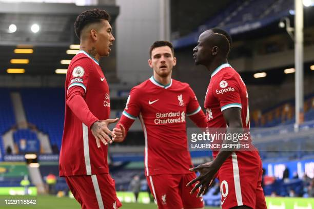 Liverpool's Senegalese striker Sadio Mane celebrates with Liverpool's Brazilian midfielder Roberto Firmino after scoring his team's first goal during...