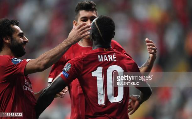 Liverpool's Senegalese striker Sadio Mane celebrates with teammates Liverpool's Egyptian midfielder Mohamed Salah and Liverpool's Brazilian...