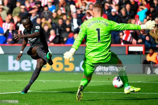 Liverpool's Senegalese striker Sadio Mane shoots past Sheffield United's English goalkeeper Dean Henderson but hits the post missing the chance...