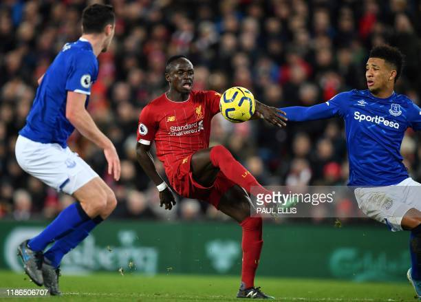 Liverpool's Senegalese striker Sadio Mane vies with Everton's English defender Michael Keane and Everton's English striker Dominic CalvertLewin...