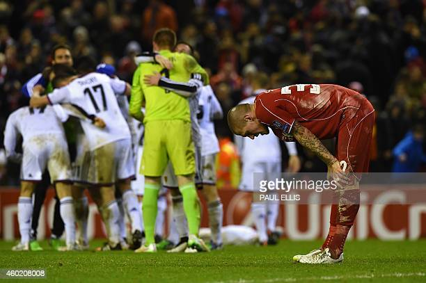 Liverpool's Slovakian defender Martin Skrtel catches his breath as the Basel players celebrate in the background during the UEFA Champions League...