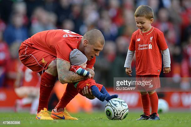 Liverpool's Slovakian defender Martin Skrtel with his son Matteo and a unidentified baby play on the pitch at the end of the English Premier League...