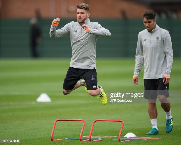 Liverpool's Spanish defender Alberto Moreno and Liverpool's Brazilian midfielder Roberto Firmino attend a team training session at their Melwood...