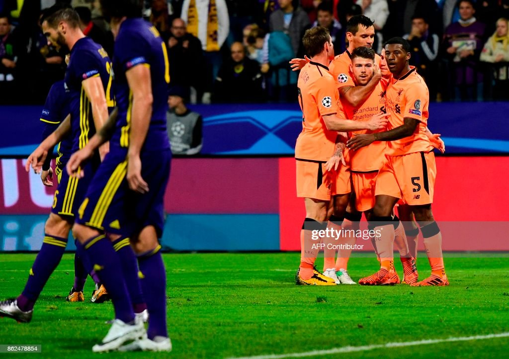 Liverpool's Spanish defender Alberto Moreno (C) celebrates with teammates after passing the ball to Liverpool's Egyptian forward Mohamed Salah (unseen) who scored during the UEFA Champions League group E football match between NK Maribor and Liverpool at the Ljudski vrt Stadium, in Maribor, on October 17, 2017. / AFP PHOTO / Jure Makovec