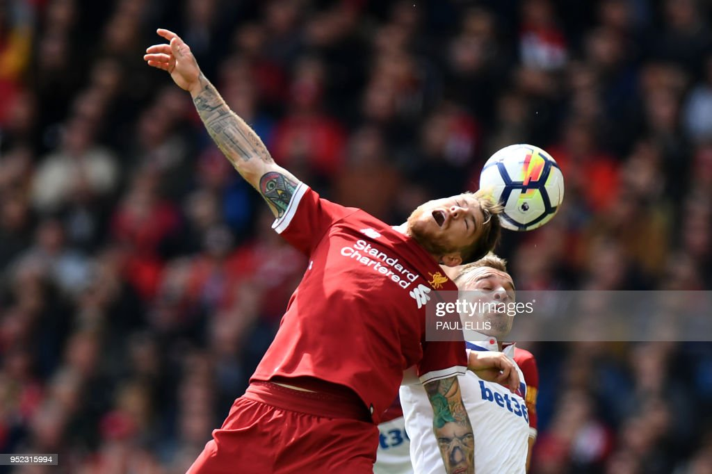 Liverpool's Spanish defender Alberto Moreno (L) heads the ball past Stoke City's English striker Peter Crouch during the English Premier League football match between Liverpool and Stoke City at Anfield in Liverpool, north west England on April 28, 2018. (Photo by Paul ELLIS / AFP) / RESTRICTED TO EDITORIAL USE. No use with unauthorized audio, video, data, fixture lists, club/league logos or 'live' services. Online in-match use limited to 75 images, no video emulation. No use in betting, games or single club/league/player publications. /