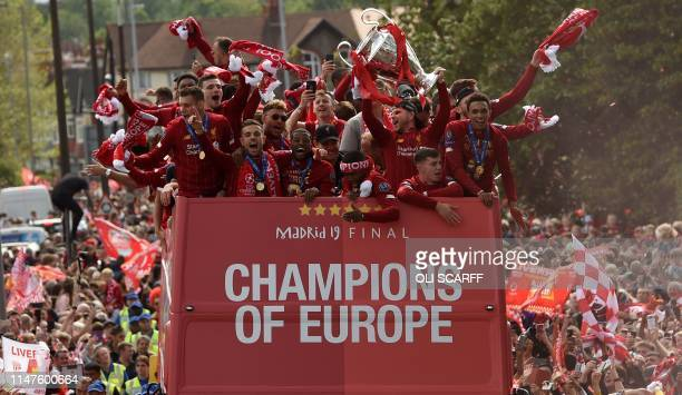 Liverpool's Spanish defender Alberto Moreno holds aloft the European Champion Clubs' Cup trophy as he stand with teammates Liverpool's English...