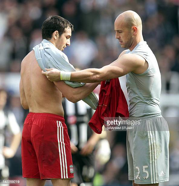 Liverpool's Spanish defender, Jose Enrique receives the goalkeeper's jersey from Spanish goalkeeper, Pepe Reina who was sent-off against Newcastle...