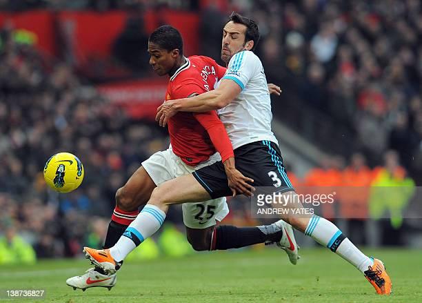 Liverpool's Spanish defender Jose Enrique vies with Manchester United's Ecuadorian midfielder Antonio Valencia during the English Premier League...