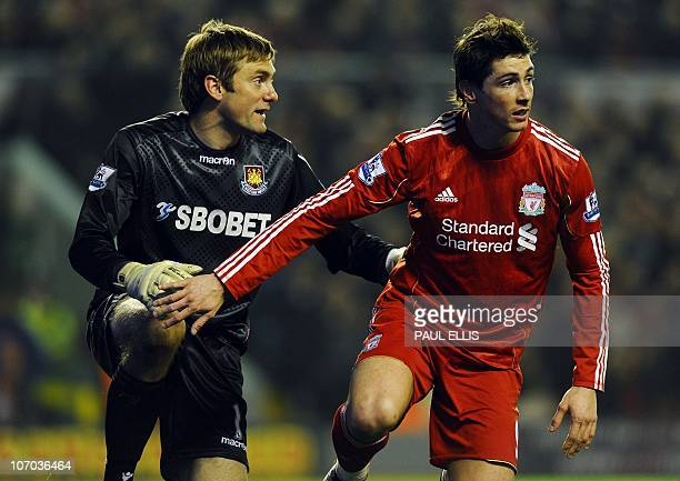 Liverpool's Spanish forward Fernando Torres and West Ham United's English goalkeeper Robert Green stand up after a challenge during their English...