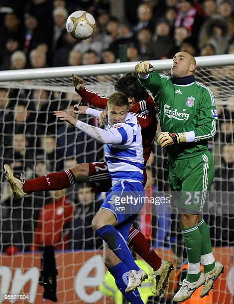 Liverpool's Spanish goalkeeper Pepe Reina punches the ball clear as Reading's English defender Matthew Mills and Liverpool's Argentine defender...