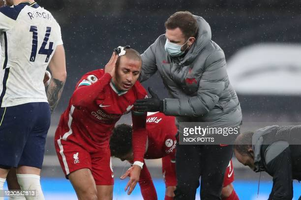 Liverpool's Spanish midfielder Thiago Alcantara gets attention after a clash of heads during the English Premier League football match between...