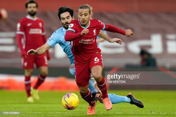 Liverpool's Spanish midfielder Thiago Alcantara runs away from Manchester City's German midfielder Ilkay Gundogan during the English Premier League...