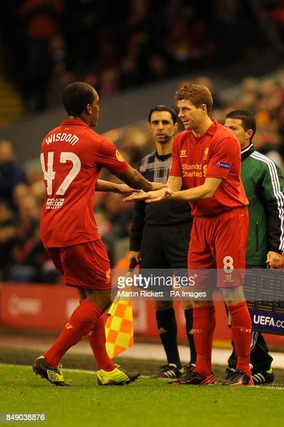 Liverpool's Steven Gerrard greets teammate Andre Wisdom whilst being substituted