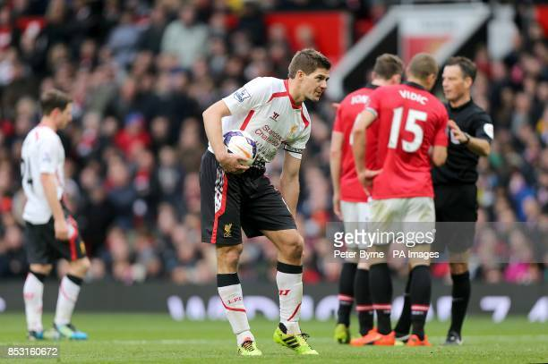 Liverpool's Steven Gerrard prepares to take his penalty as Manchester United's Phil Jones and Nemanja Vidic argue with referee Mark Clattenburg in...