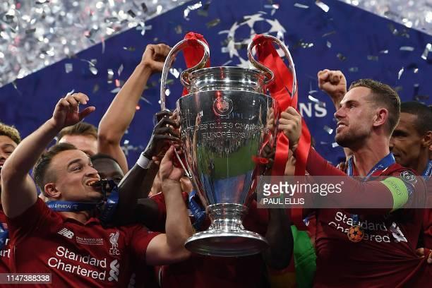 Liverpool's Swiss midfielder Xherdan Shaqiri and Liverpool's English midfielder Jordan Henderson raise the European Champion Clubs' Cup as they...