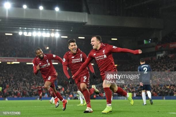 Liverpool's Swiss midfielder Xherdan Shaqiri celebrates with Liverpool's Dutch midfielder Georginio Wijnaldum and Liverpool's Brazilian midfielder...